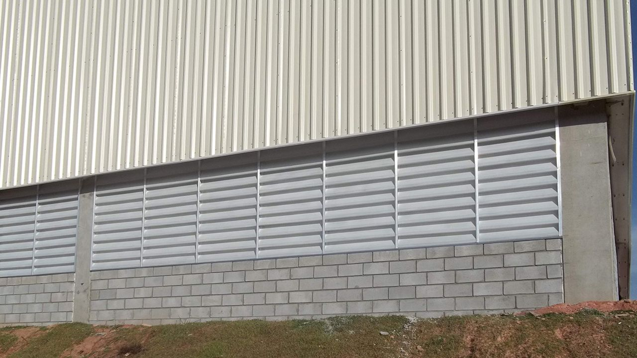 Exemplo de galpão industrial com venezianas no fechamento lateral.