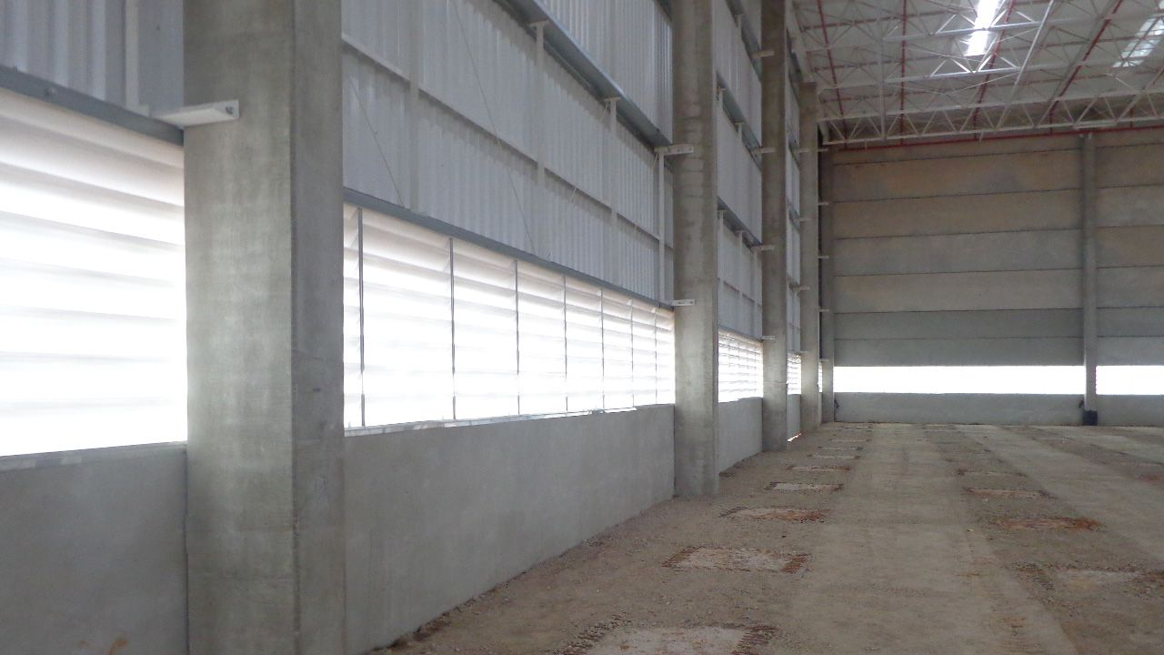 Vista interna de galpão industrial com venezianas no fechamento lateral, com excelente luminosidade.